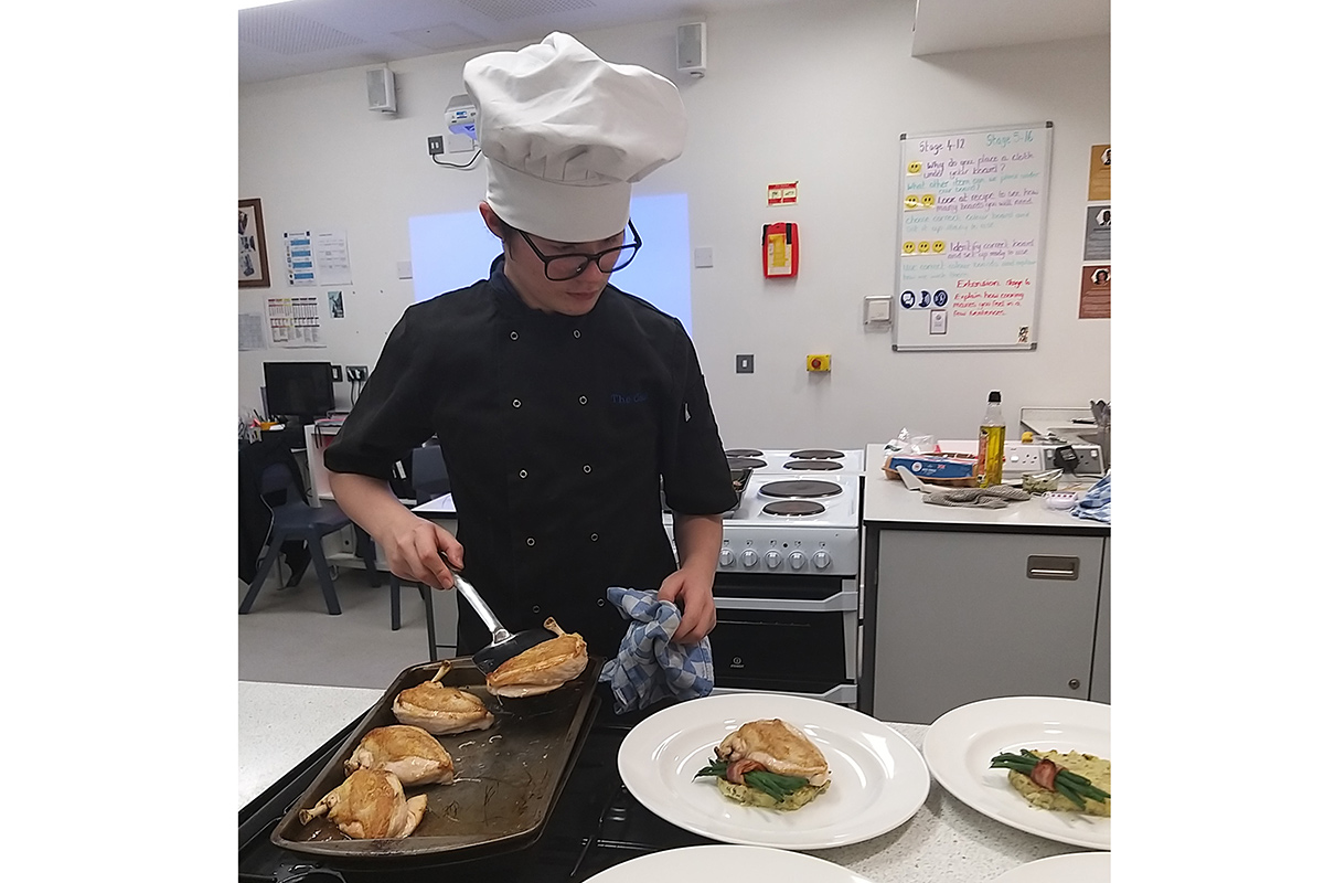 Student plating up a chicken main course