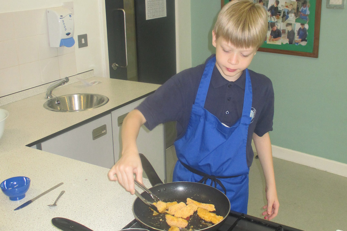 Student pan frying home made chicken goujons